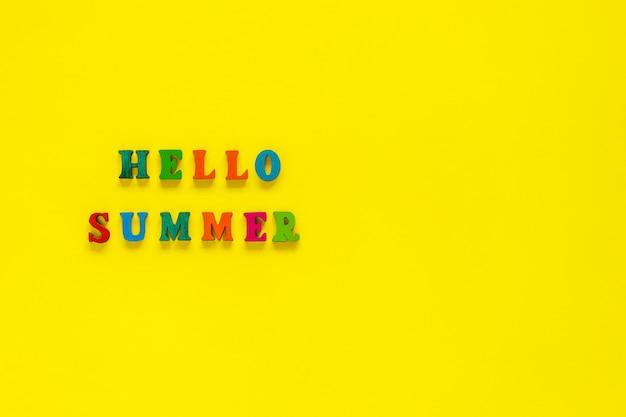 黄色の背景にカラフルな文字から碑文こんにちは夏 Premium写真