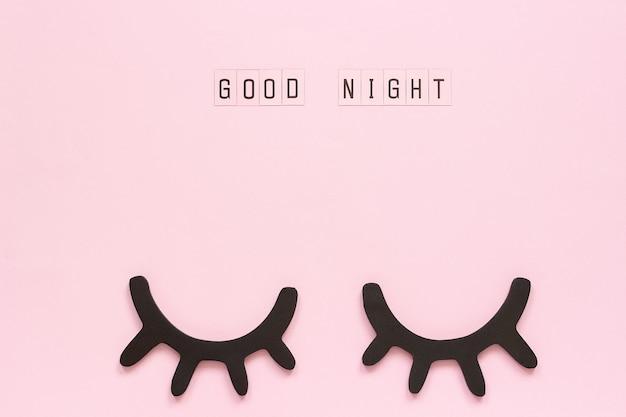 テキストおやすみと装飾的な木製黒まつげ、ピンクの紙の背景に目を閉じた。 Premium写真