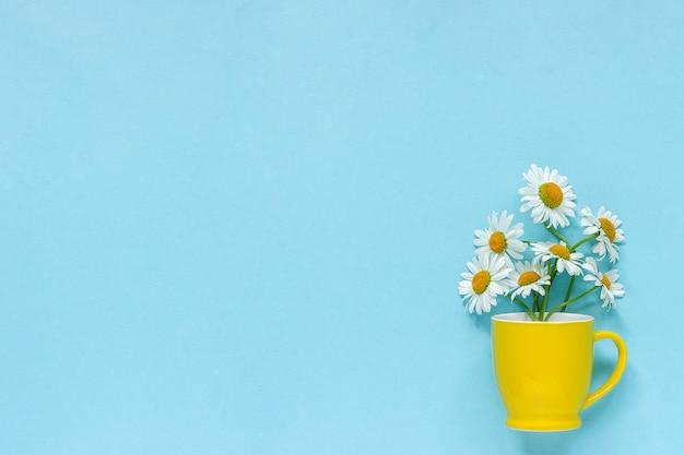 Букет ромашки ромашки цветы в желтой кружке на пастельно-синем фоне Premium Фотографии