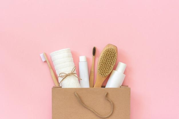 エコ化粧品とシャワーやピンクの背景に紙袋のお風呂用のツールのセットです。 Premium写真