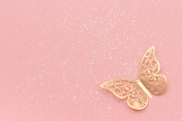 ピンクのパステル調のトレンディな背景に輝くキラキラとゴールドの網目模様の蝶。 Premium写真