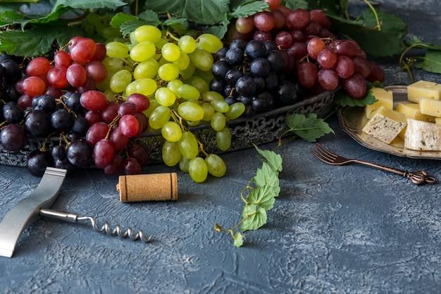 明るい、赤と濃いぶどう、コルク抜き、ワインのコルクと銀の皿にチーズとフォークのブラシ Premium写真