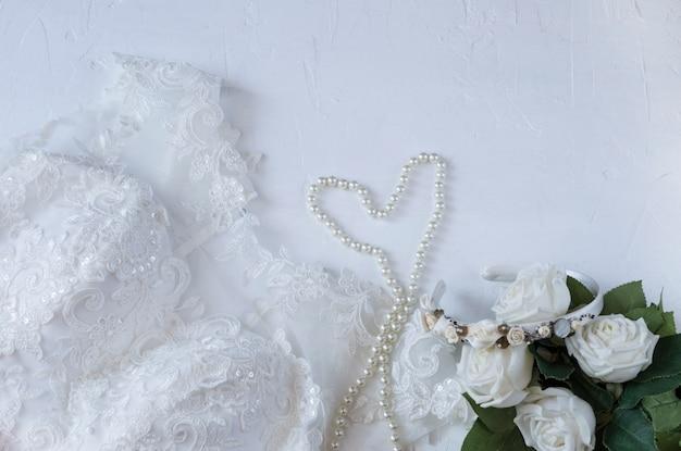 花嫁の結婚式の準備:ドレス、真珠、バラ Premium写真