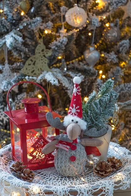 ランタン、クリスマスツリーの下のトウヒとおもちゃのムースの枝 Premium写真