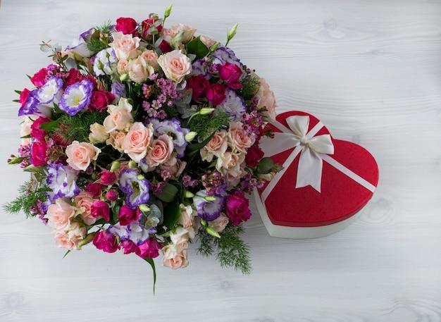 テーブルの上に花とギフトの美しい花束 Premium写真
