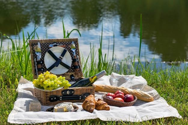 湖でのピクニック:テーブルクロス、食器、バゲット、ぶどう、桃のピクニックバスケット Premium写真