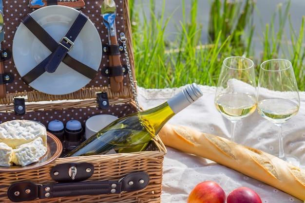 湖でのピクニック:テーブルクロス、食器付きピクニックバスケット、バゲット Premium写真