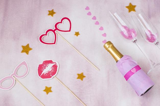 На розовом фоне бутылка шампанского, праздничные наклейки и розовые сердечки - девичник Premium Фотографии