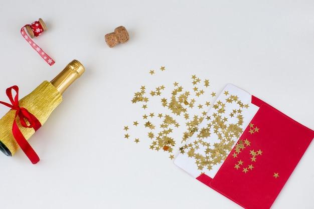 Красный конверт, золотые звезды, красная лента и бутылка шампанского Premium Фотографии