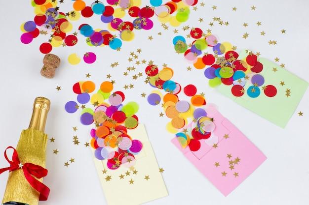 Три конверта на белом фоне, из них летят цветные конфетти, бутылка шампанского Premium Фотографии