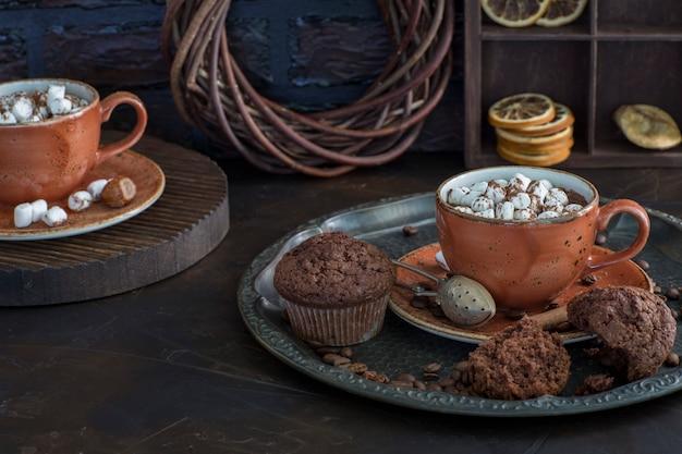 Две чашки горячего шоколада с зефиром и кексы крупным планом Premium Фотографии