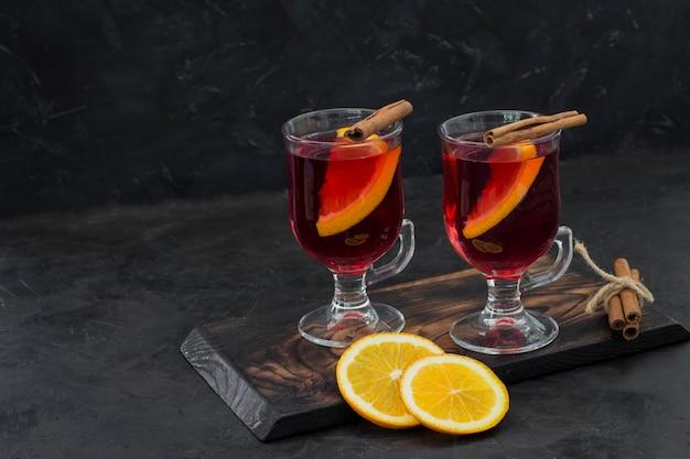 シナモンとオレンジの透明な円で熱い赤い飲み物 Premium写真