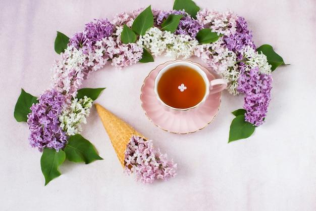 ライラックのアーチ、お茶とアイスクリームのワッフルコーンにライラックの枝 Premium写真