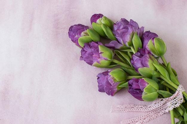 Фиолетовые тюльпаны, перевязанные кружевной лентой Premium Фотографии