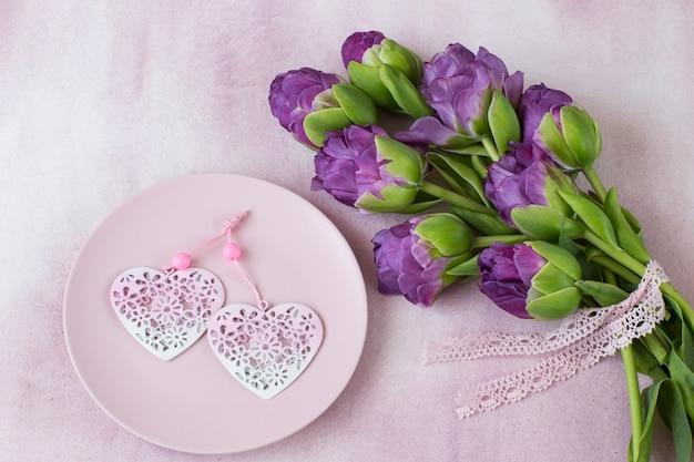 Фиолетовые тюльпаны и два сердца в розовой тарелке Premium Фотографии