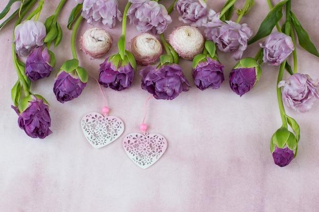 Подряд фиолетовые тюльпаны и два розовых сердца Premium Фотографии