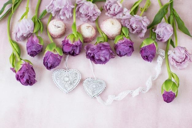 Ряд - фиолетовые тюльпаны, лента из кружева и два сердца Premium Фотографии