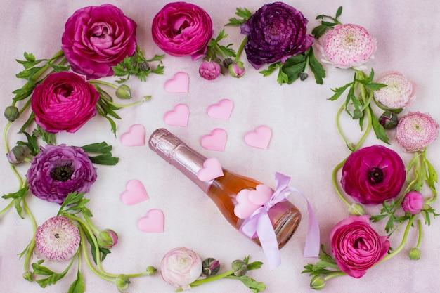 ラナンキュラスとサテンのシャンパンとピンクのハートのボトル Premium写真