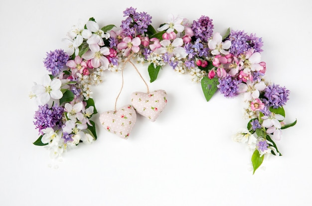 Цветы черемухи, сирени и яблони, выложенные аркой и двумя сердечками из ткани Premium Фотографии