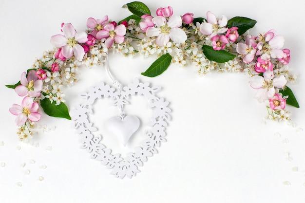 鳥の桜とりんごの木の花にはアーチと白い網目模様の心が並んでいます。 Premium写真