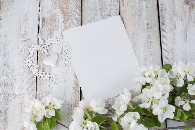 開花のリンゴの木、一枚の紙と幾何学模様の心の枝 Premium写真