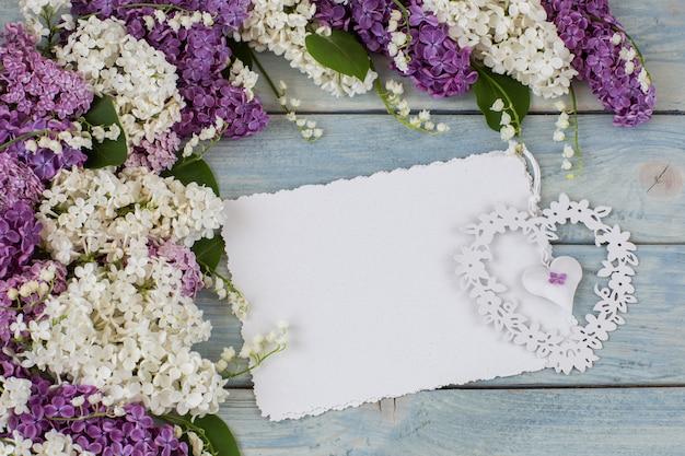 Белая и фиолетовая сирень, ландыши, лист бумаги и сердце Premium Фотографии