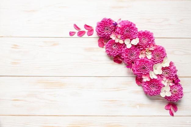 白い木製の背景にピンクのダリアと秋の花柄。 Premium写真