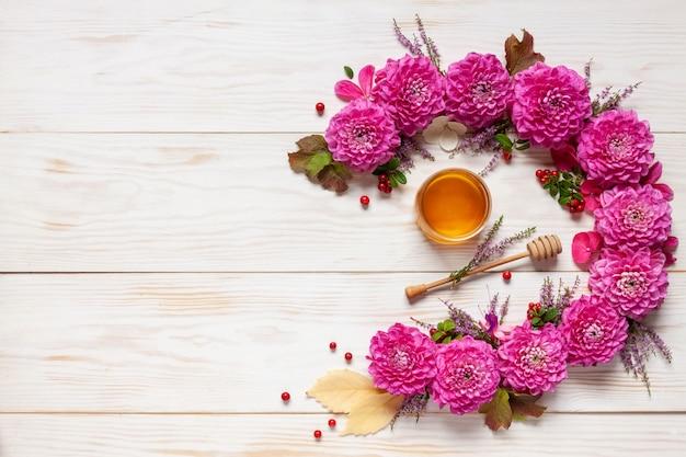 花飾り。ピンクのダリア、紅葉、コケモモ、蜂蜜入り Premium写真