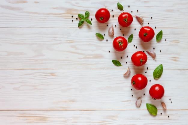 Красивые свежие сырые помидоры, базилик и чеснок. Premium Фотографии