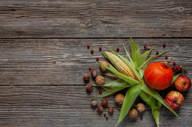 トウモロコシ、カボチャ、リンゴ、ナッツヴィンテージの木製の背景に。 Premium写真