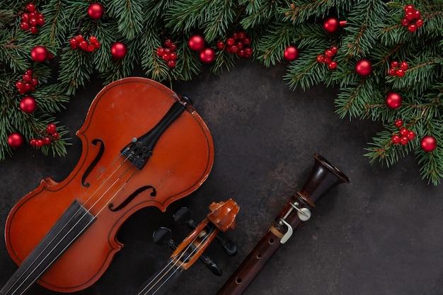 古いバイオリンとフルート、クリスマスデコレーションのモミの木の枝。トップビュー、クローズアップ Premium写真