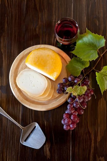 Красный виноград с листьями, бокал вина и свежий сыр на деревенском деревянном. вид сверху, крупный план. Premium Фотографии