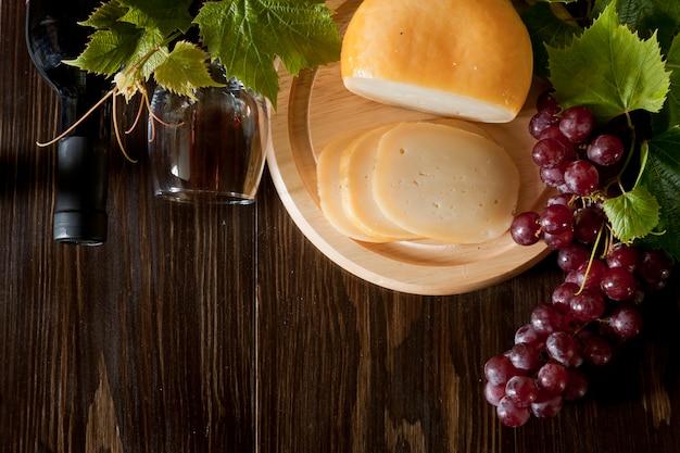 Красный виноград с листьями, бокал вина и свежий сыр. вид сверху, крупный план. Premium Фотографии