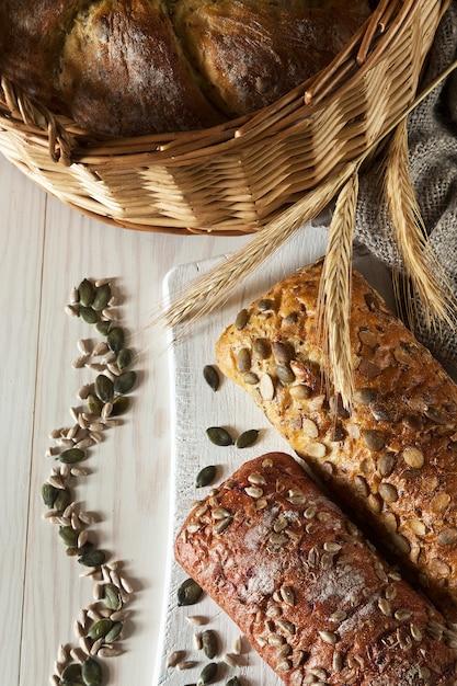 Разные виды хлеба с семенами на белой деревянной предпосылке. Premium Фотографии