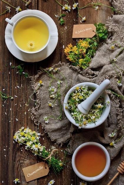 Ромашковый чай с натуральным медом, ромашкой в ступке и гроздьями зверобоя Premium Фотографии