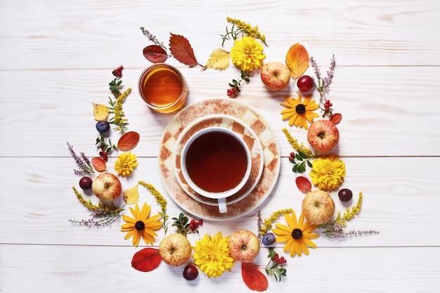 りんご、プラム、新鮮な蜂蜜、ティーカップ、赤い果実、そして美しい花 Premium写真