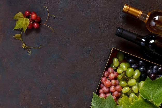 Красный, зеленый и синий виноград с листьями в металлической коробке и две бутылки вина. Premium Фотографии