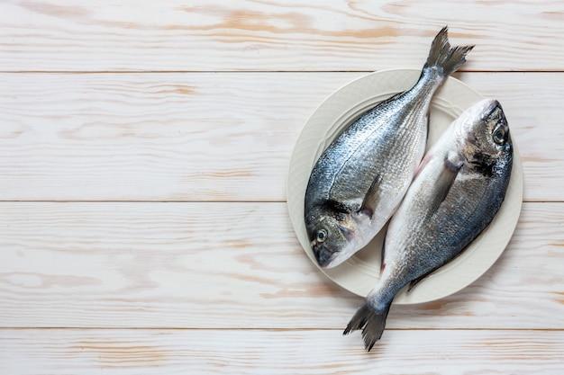 白いテーブルの上の白い皿に新鮮なドラド魚。 Premium写真