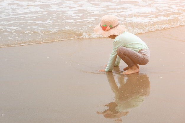 砂のビーチでビーチおもちゃで遊ぶ愛らしい幼児の女の子 Premium写真