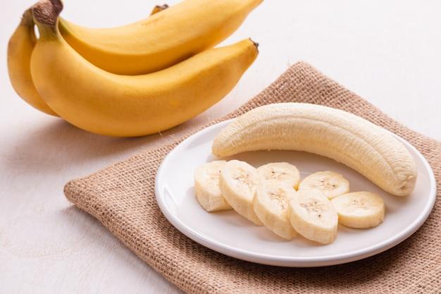 Бананы в тарелке (красивая форма) на белой древесине Premium Фотографии