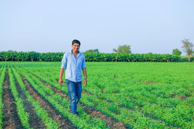 Молодой индийский фермер на пшеничном поле Premium Фотографии