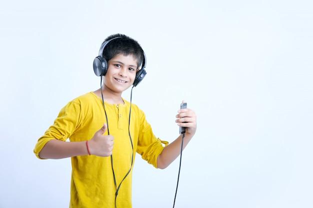 ヘッドフォンで音楽を聴く若いインドのかわいい男の子 Premium写真