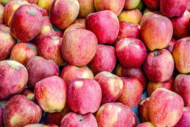 Куча целого спелого яблока на фруктовом рынке Premium Фотографии