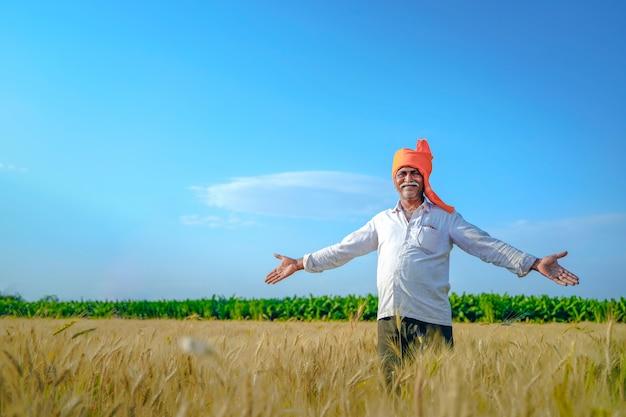 幸せなインドの農家が歩いて、彼の麦畑で彼の腕を広げています。 Premium写真