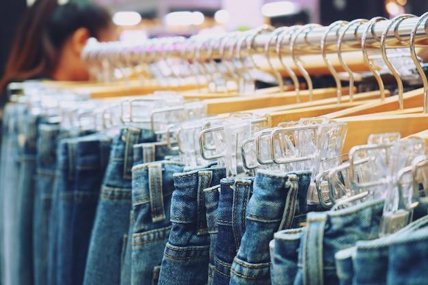 Многие джинсы висят на стойке в магазине Premium Фотографии