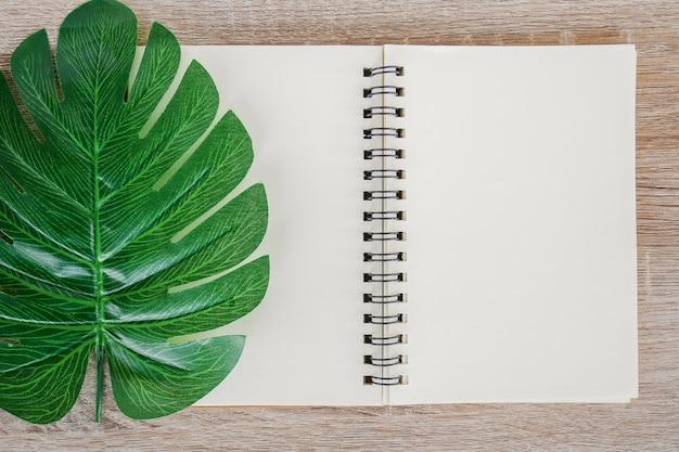 緑の熱帯モンステラと木製の机の背景に空白のノートブックを開くの平面図です。 Premium写真
