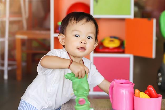 Счастливая азиатская девушка ребенка усмехаясь и играя с много игрушек на комнате. Premium Фотографии