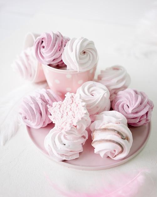 白地にピンクと白のメレンゲ。水玉模様のカップ Premium写真