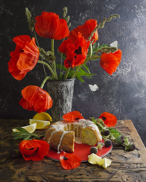 自家製レモンケーキと赤い花。飛んでいる蝶 Premium写真