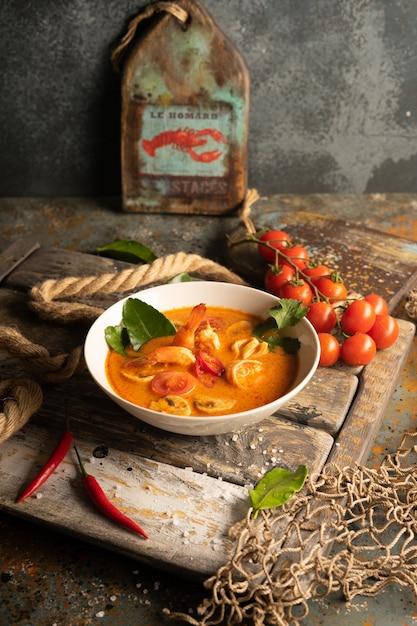 Суп том ям с креветками, кальмарами и острым перцем на текстурированной деревянной доске Premium Фотографии